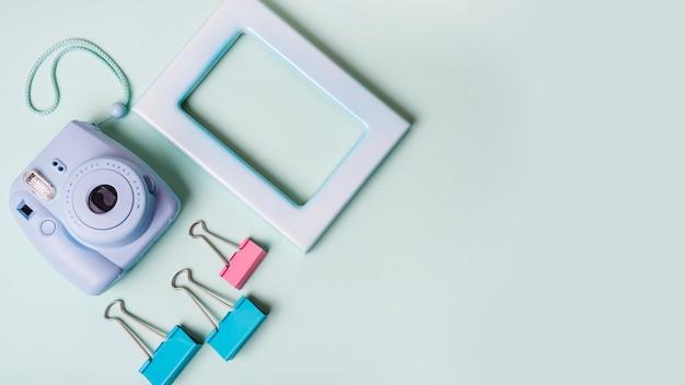 Mini câmera instantânea; clipes de papel e moldura em fundo colorido