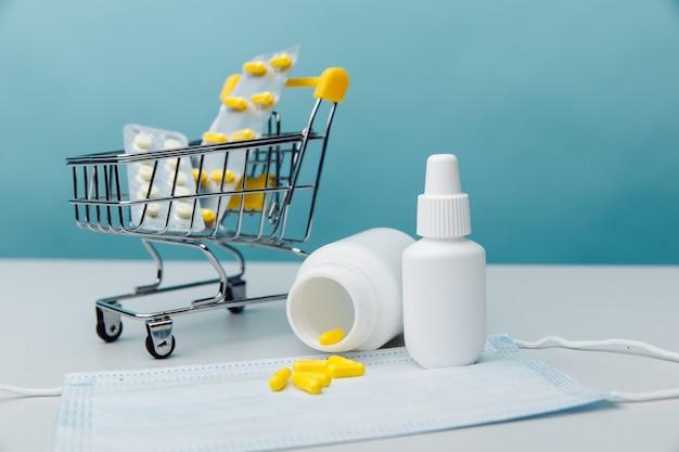 Mini carrinho com comprimidos e ferramentas médicas em um conceito de compras on-line de fundo azul