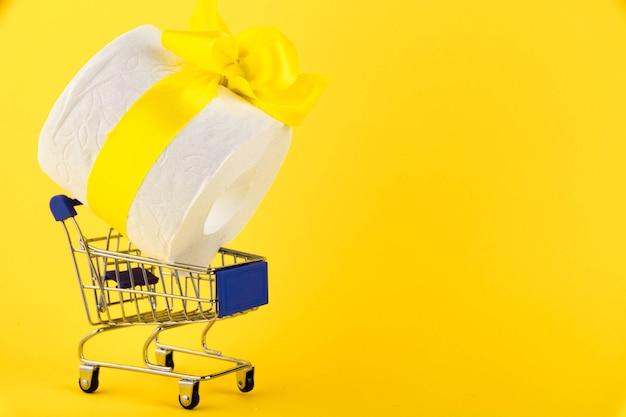 Mini carrinho de compras, cesto de compras, rolo de papel higiênico branco com laço amarelo para presente sobre fundo amarelo. copie o espaço