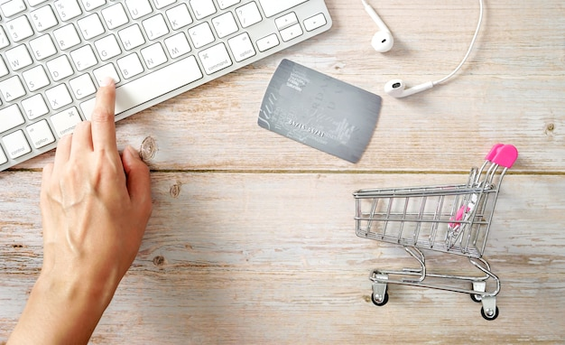 Mini carrinho de compras com as mãos digitando o teclado do laptop com um cartão de crédito borrado pagamento online