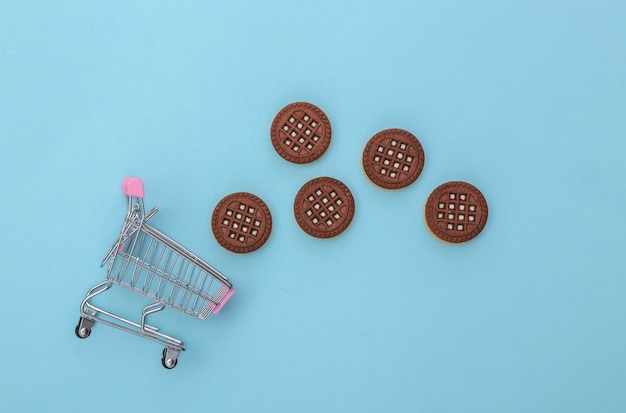 Mini carrinho de compras com biscoitos de chocolate em um fundo azul. vista do topo
