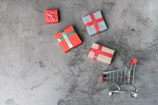 Mini carrinho de compras com caixas de presente.