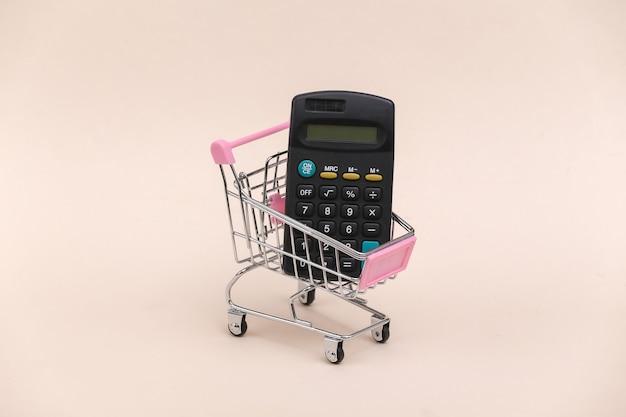 Mini carrinho de compras com calculadora em fundo bege