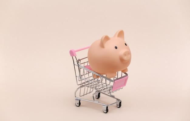 Mini carrinho de compras com cofrinho em fundo bege