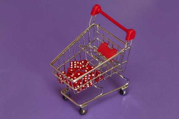 Mini carrinho de compras com dadinhos vermelhos, conceito de jogo Foto Premium