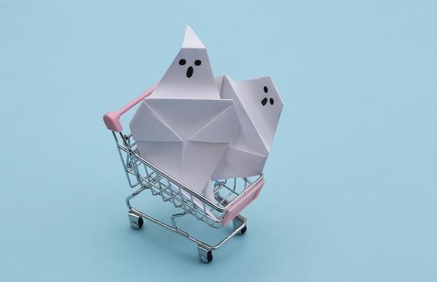 Mini carrinho de compras com fantasmas de origami em fundo azul. tema de halloween
