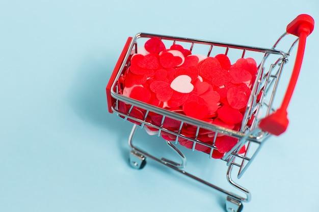 Mini carrinho de compras com muitos corações vermelhos na superfície azul