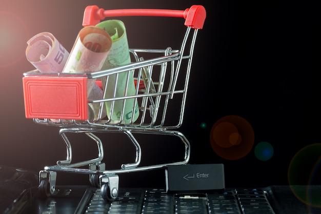 Mini carrinho de compras com notas e moedas no teclado do laptop