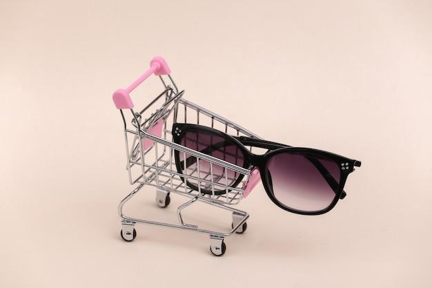 Mini carrinho de compras com óculos de sol em fundo bege