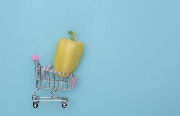 Mini carrinho de compras com pimentão sobre fundo azul. vista do topo