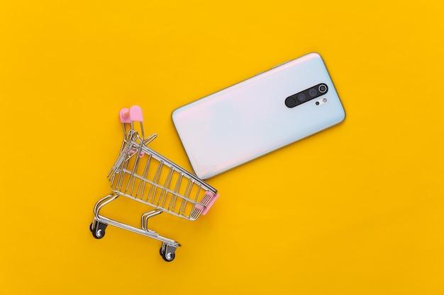Mini carrinho de compras com smartphone em amarelo