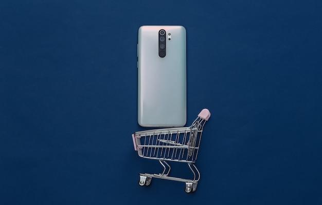 Mini carrinho de compras com smartphone em azul clássico