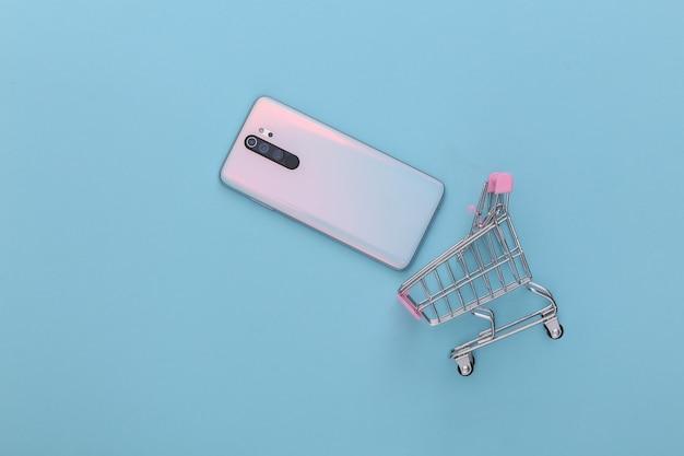 Mini carrinho de compras com smartphone em azul