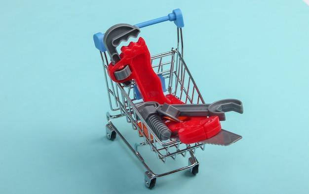 Mini carrinho de compras com uma ferramenta de brinquedo em um fundo azul pastel