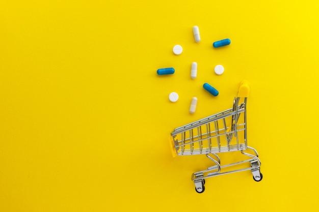 Mini carrinho de compras, comprimidos e cápsulas em fundo amarelo