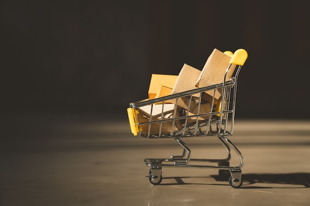 Mini carrinho de compras contém caixa de papel usando como e-commerce
