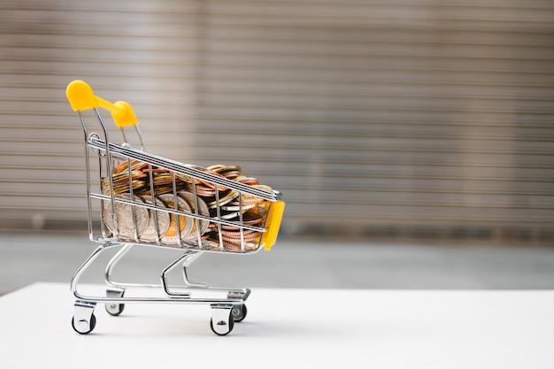 Mini carrinho de compras contém moedas de pilha usando como e-commerce e conceito de marketing de negócios