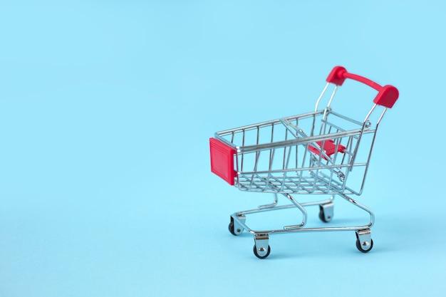 Mini carrinho de compras de metal vazio sobre fundo azul