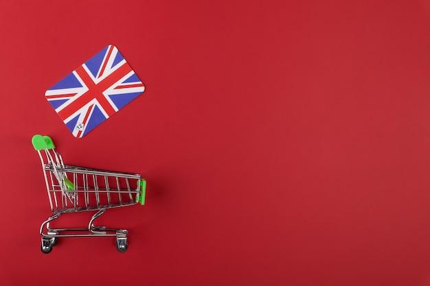 Mini carrinho de compras de supermercado vazio, bandeira do reino unido sobre fundo vermelho
