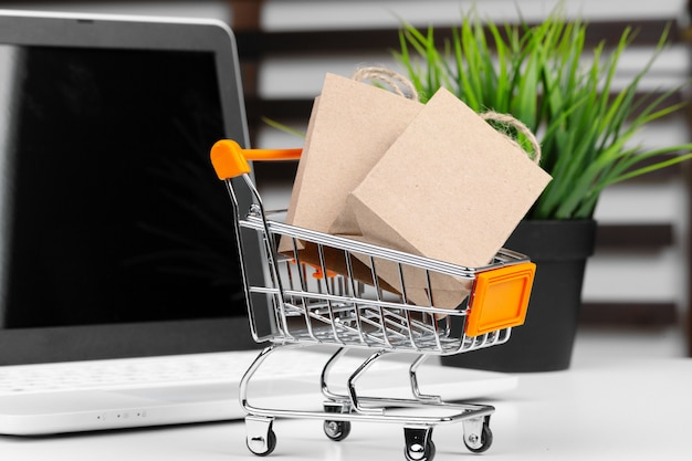 Mini carrinho de compras e laptop na mesa