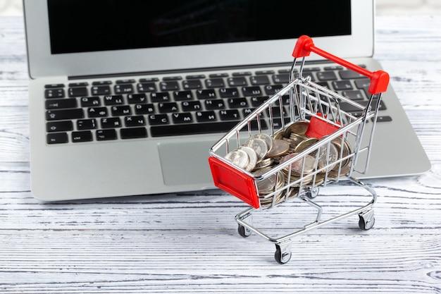Mini carrinho de compras e laptop