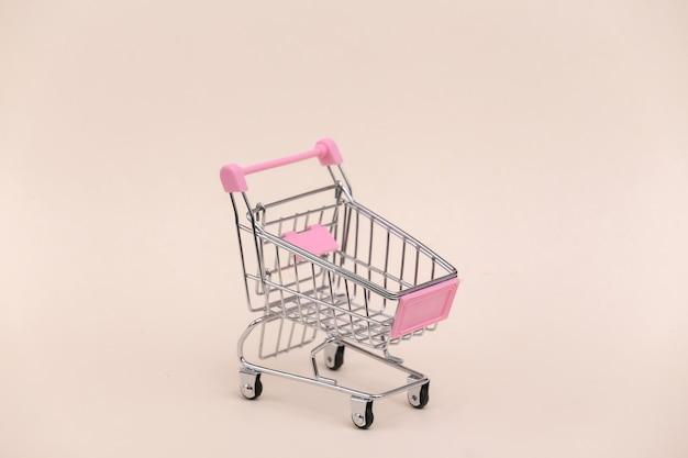 Mini carrinho de compras em fundo bege