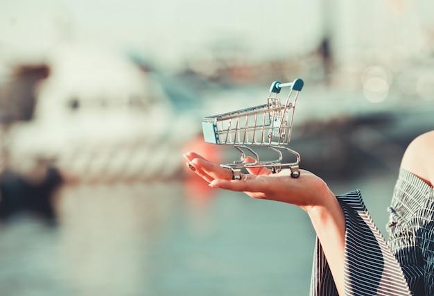 Mini carrinho de compras fica na palma da mão de uma mulher ao ar livre