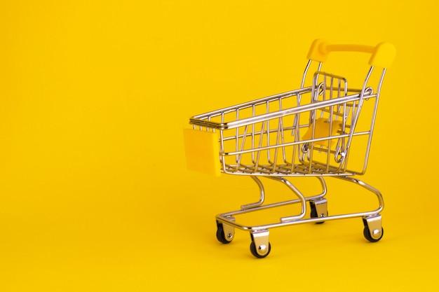 Mini carrinho de compras isolado em fundo amarelo. carrinho de supermercado vazio. comprando o conceito online. copie o espaço