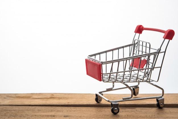 Mini carrinho de compras na mesa para o trabalho para o trabalho ao conceito on-line de compras