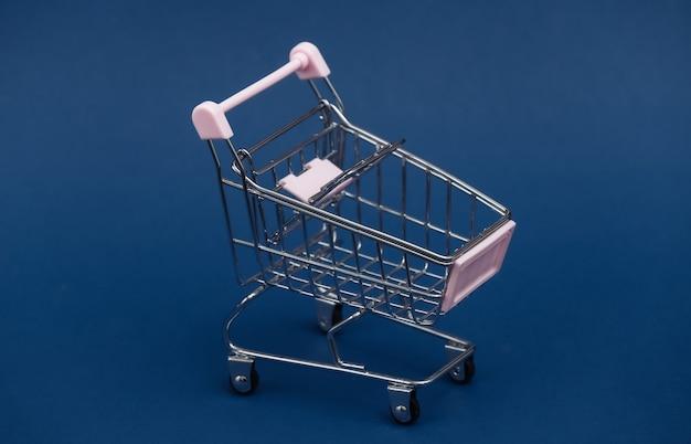 Mini carrinho de compras no fundo azul clássico