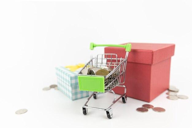 Mini carrinho de compras prateado com moedas no carrinho e caixa vermelha em branco.