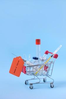 Mini carrinho de salto com seringas, injeções, vacinas e tubos de sangue sobre fundo azul e inscrição pare o vírus. conceito de vacinação