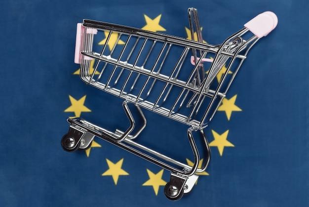 Mini carrinho de supermercado no fundo desfocado da bandeira da união do euro. conceito de compras.