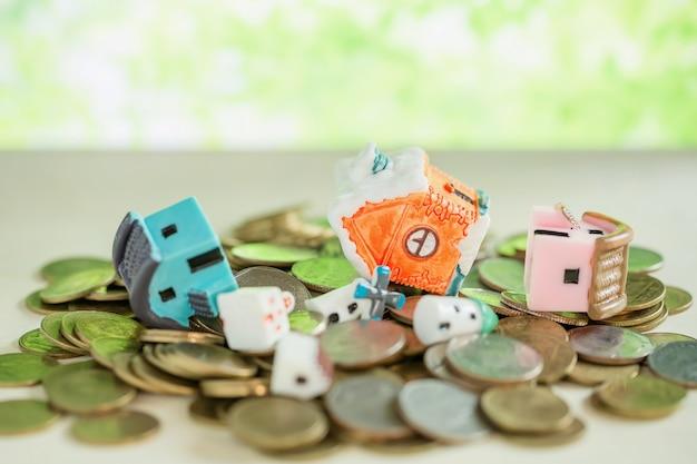 Mini casa na pilha das moedas com borrão verde.