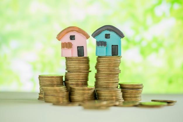 Mini casa na pilha de moedas com borrão verde.