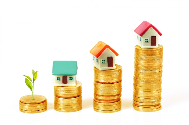 Mini casa na pilha de moedas com despertador e planta crescer