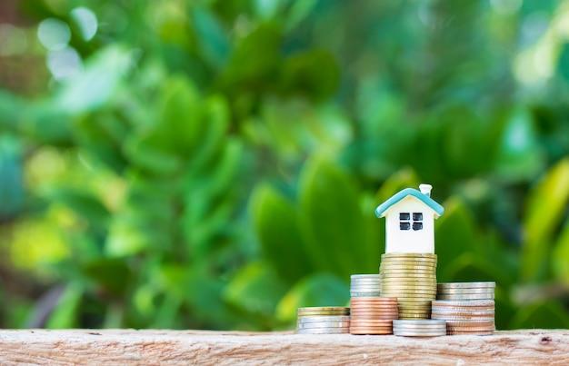 Mini casa na pilha de moedas. conceito de propriedade para investimento.