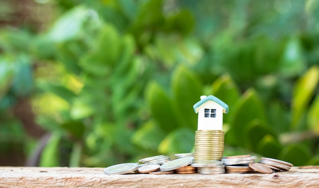 Mini casa na pilha de moedas na natureza turva
