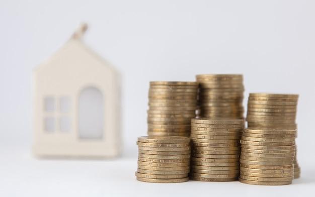 Mini casa na pilha de moedas