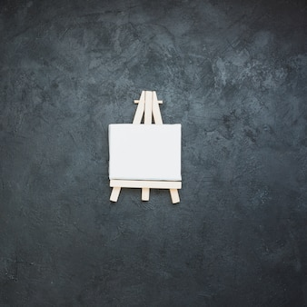 Mini cavalete branco em branco na superfície da ardósia preta