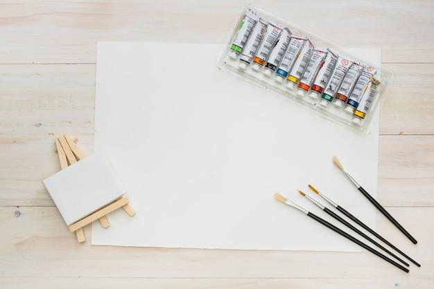 Mini cavalete com papel em branco; escovas e tubo de tinta no pano de fundo