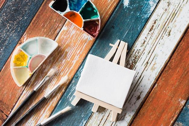 Mini cavalete em branco e equipamentos de pintura na velha mesa de madeira colorida