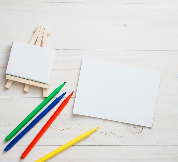 Mini cavalete em branco; papel branco e cores caneta de ponta de feltro sobre o pano de fundo de textura de madeira