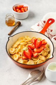 Mini cereal panqueca branca com morangos na frigideira no café da manhã no fundo cinza. café da manhã em casa moderno com pequenas panquecas. vista do topo.