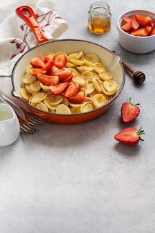Mini cereal panqueca branca com morangos na frigideira no café da manhã no fundo cinza.