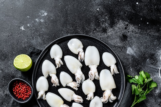 Mini choco cru com alecrim e salsa em um prato. superfície preta. vista do topo. copie o espaço