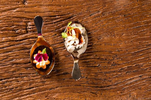 Mini churros salgados e porco caramelizado acompanhado de arroz de jasmim e curry vermelho na colher. prove petiscos gastronômicos