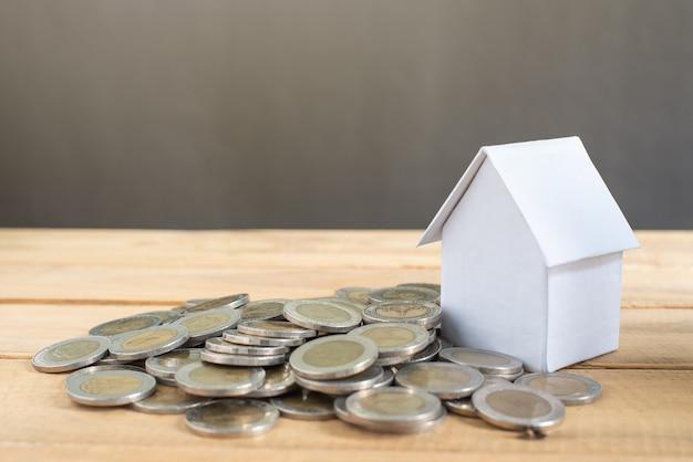 Mini cor branca do modelo da casa com muitas moedas na tabela de madeira e no fundo preto. salvando o conceito de dinheiro para casa. negócios, finanças, bancos e imóveis avançam e crescem
