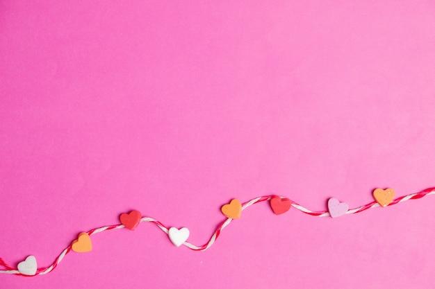 Mini corações com corda em fundo rosa em branco