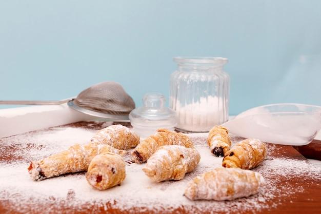 Mini croissant caseiros em uma mesa de cozinha de madeira.